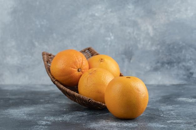 Un cesto di vimini pieno di frutti d'arancia.