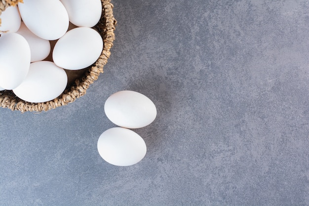 Wicker basket full of organic eggs on stone table.