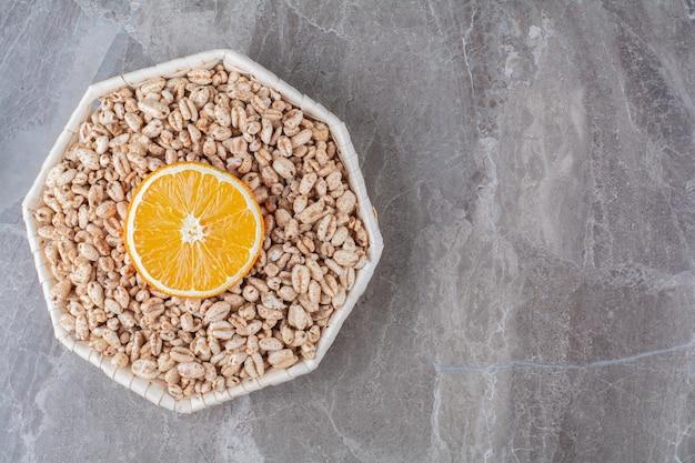 Un cesto di vimini di cereali per la colazione di riso croccante sano con una fetta di frutta arancione.