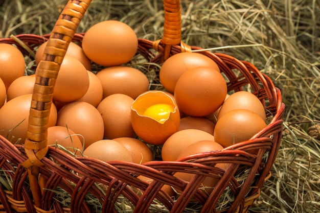 In a wicker basket near the hay lay eggs and one of them is seen yolk