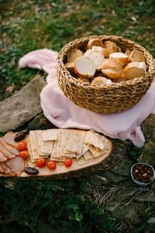 木製のスタンドとビスケットビスケット、トマト、ハムが置かれた地面のベッドに籐のパンのバスケット。高品質の写真