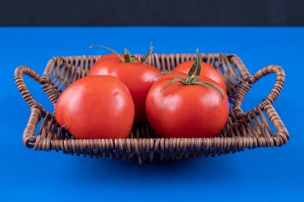 푸른 표면에 신선한 빨간 토마토의 고리 버들 세공 바구니