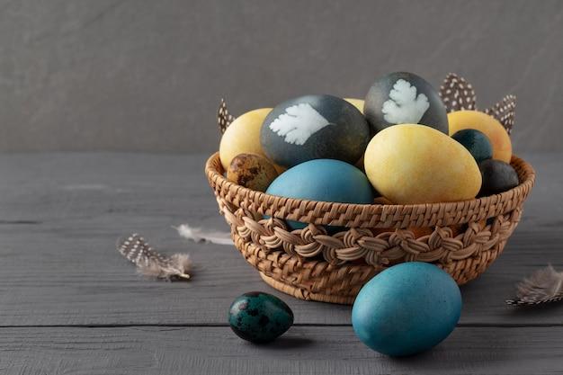 灰色の木製テーブルに葉の痕跡が描かれたイースターエッグの籐のバスケット