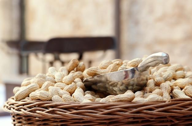 屋外市場での金属スクープ付きの殻付き生有機ピーナッツの枝編み細工品バスケット、コピースペース。地元の市場で販売されている皮をむいていない落花生、クローズアップビュー。健康的な野菜料理 Premium写真