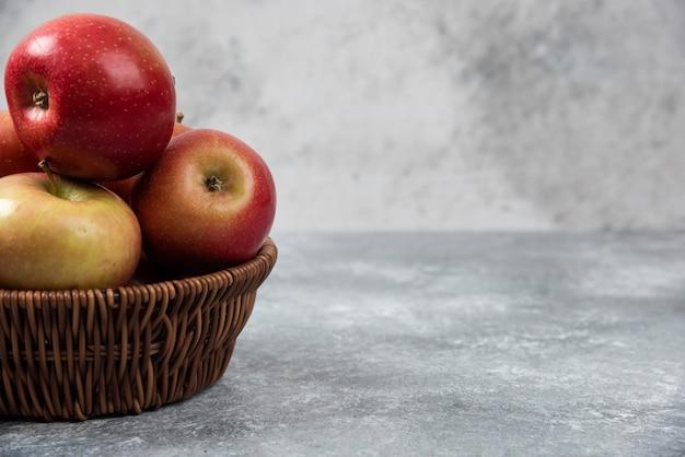 大理石の表面に赤いジューシーなリンゴの籐のバスケット。