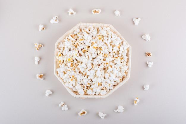 白い背景の上の映画の夜のための塩味のポップコーンの籐のバスケット。高品質の写真