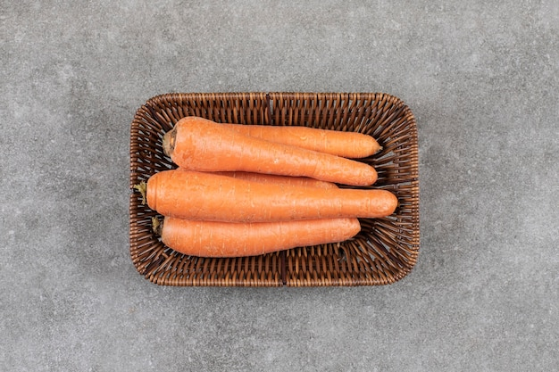 Плетеная корзина из цельной свежей моркови на мраморной поверхности.