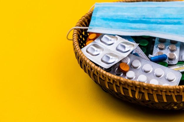 黄色の背景に枝編み細工品バスケット。バスケットのマディカルマスク。コピースペース。テキストとデザインのための場所。上面図。フラットレイアウトの丸薬とビタミン。