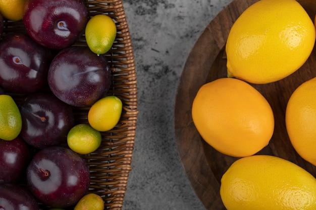 Un cesto di vimini di prugne viola e ciotola di legno con limoni.