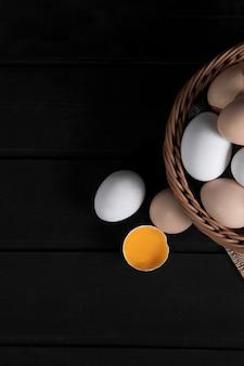 Wicker basket of raw chicken eggs on dark wooden surface. high quality photo