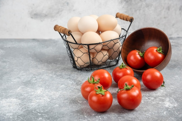 Wicker basket of raw organic eggs and bowl of tomatoes on marble.