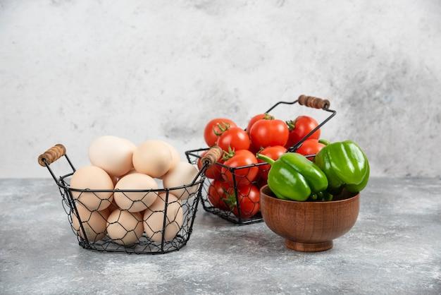 Cesto di vimini di uova biologiche crude e pomodori con peperoni su marmo.