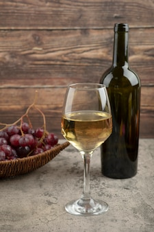 Wicker basket of red grapes with glass of white wine on marble table.