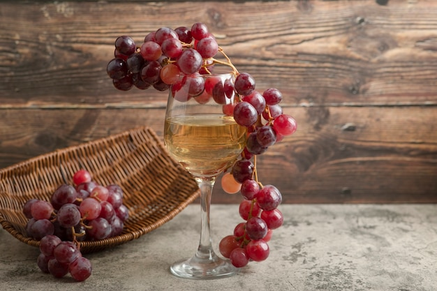 Wicker basket of red grapes with glass of wine on marble table.