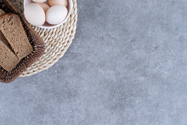 Wicker basket of rye bread and bowl of raw eggs on stone table.