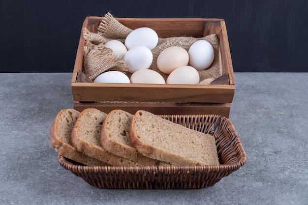 Cesto di vimini di pane di segale e scatola di legno di uova crude su pietra.