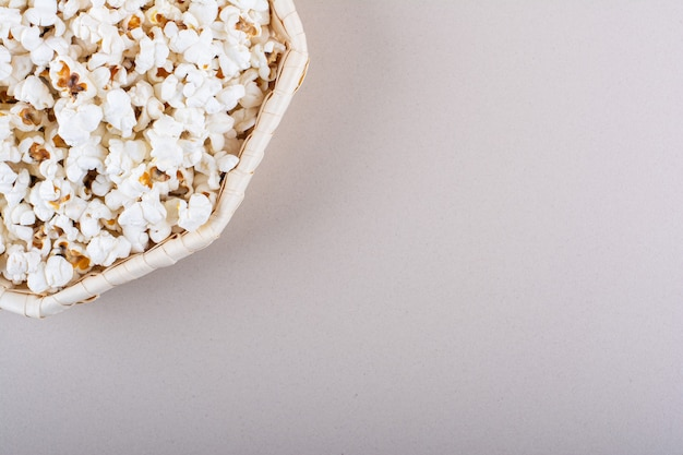Wicker basket of salted popcorn for movie night on white background. high quality photo