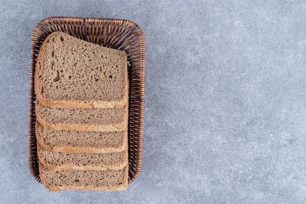 Wicker basket of sliced rye bread on stone table.