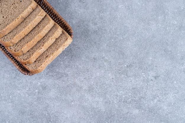 Wicker basket of sliced rye bread on stone.