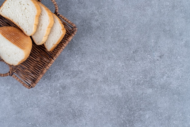 Wicker basket of sliced white bread placed on stone table.