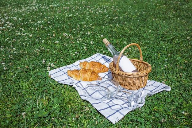 Плетеная корзина с яблоками, бутылка розового вина и два стакана на клетчатой ткани на траве в парке