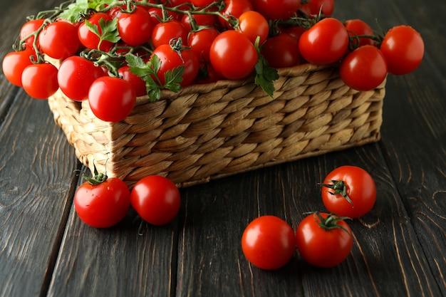 나무 바탕에 체리 토마토와 고리 버들 세공 바구니