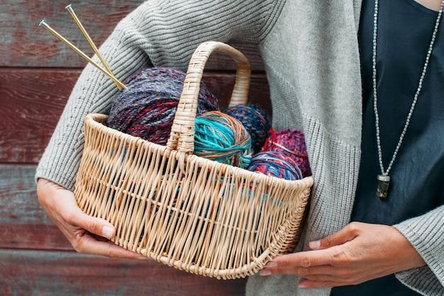 여성의 손에 뜨개질에 대 한 양모 원사의 다채로운 밝은 공 바구니. 뜨개질 실, 바늘, 실 실타래. 뜨개질에 대한 아름다운 색상. 개념 손으로 만든 창조적 인 뜨개질.