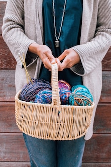 여성의 손에 뜨개질에 대 한 양모 원사의 다채로운 밝은 공 바구니.