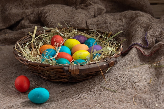 Плетеная корзина с красочными пасхальными яйцами на фоне мешковины