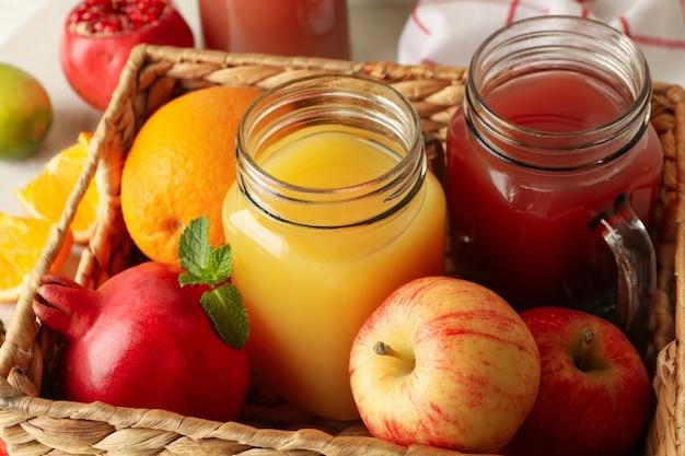 Плетеная корзина с разными соками и фруктами