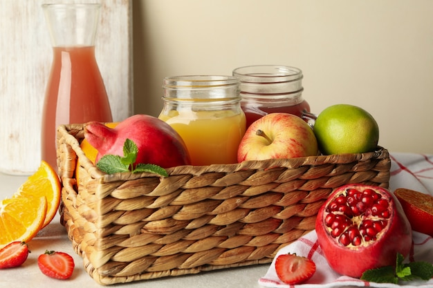 Wicker basket with different juices and fruits
