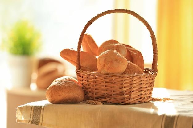 テーブルの上にさまざまな種類の焼きたてのパンが入った籐のバスケット