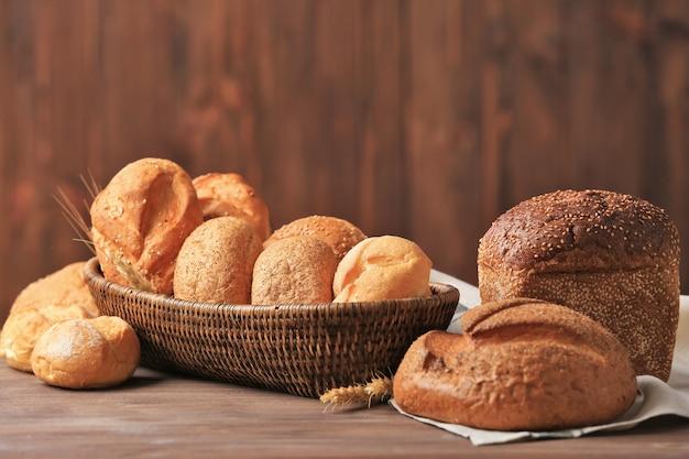 Плетеная корзина с различными видами свежего хлеба на деревянном столе