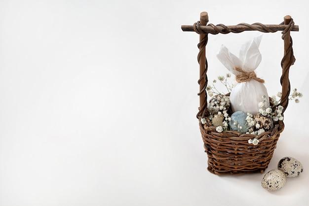 うさぎと小さな斑点のある卵と白い花として飾られたイースターエッグの籐のバスケット。ハッピーイースターグリーティングカード、招待状。テキスト用のスペース