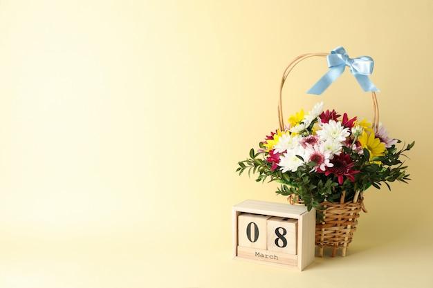 Плетеная корзина с цветами и деревянным календарем на бежевом