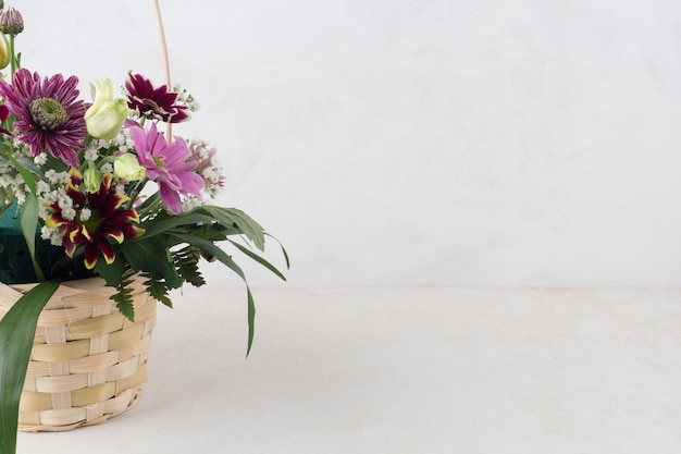 Wicker basket with flowers on grey background