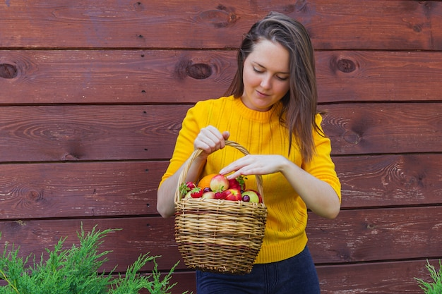 A wicker basket with fresh fruit is held by a young brunette girl