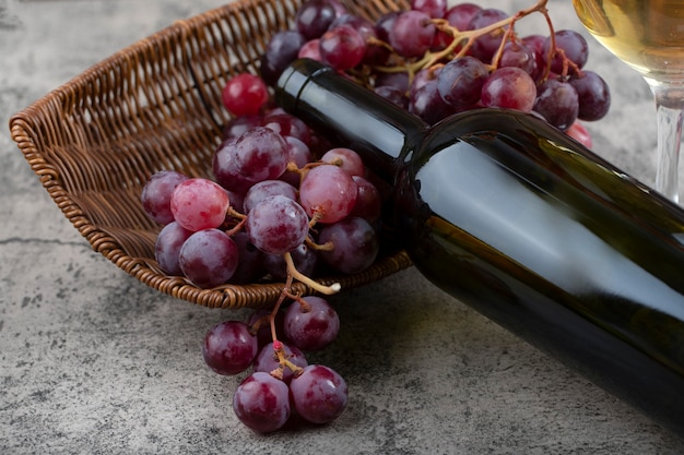 Wicker basket with fresh red grapes and white wine on stone table.