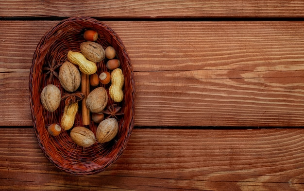 テクスチャード加工の木製の背景にヘーゼルナッツ、クルミ、ピーナッツ、スパイスが入った籐のバスケット。ビューのトップ。