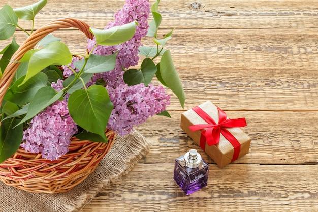 라일락 꽃이 든 고리버들 바구니, 향수 한 병, 나무 판자에 선물 상자. 복사 공간이 있는 상위 뷰입니다.