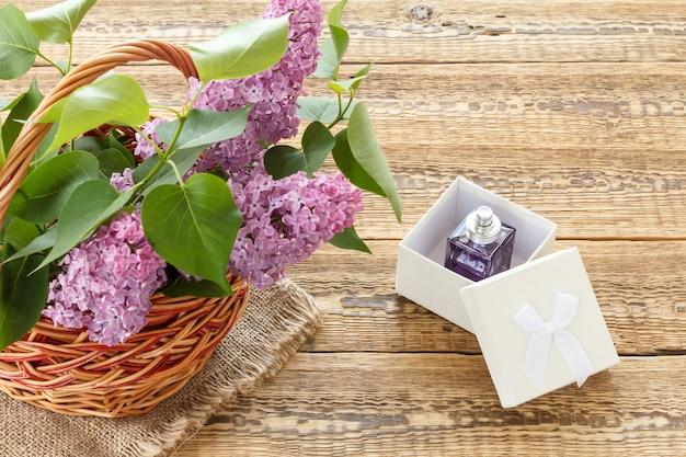 나무 판자에 향수 한 병이 든 라일락 꽃과 흰색 선물 상자가 있는 고리버들 바구니. 복사 공간이 있는 상위 뷰입니다.