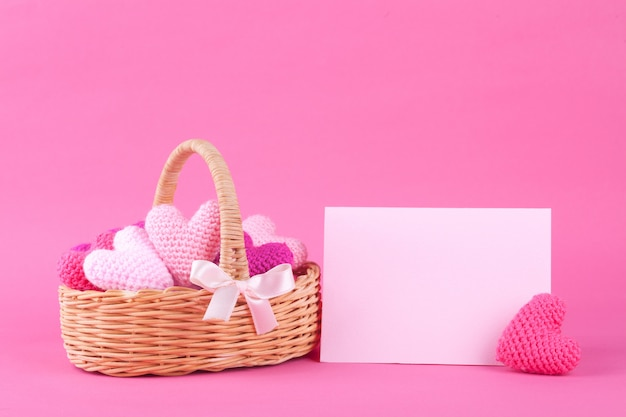Wicker basket with multi-colored knitted hearts. bright pink background. festive decor. valentine's day. diy