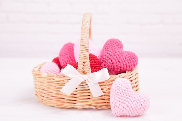 Wicker basket with multi-colored knitted hearts. festive decor. valentine's day