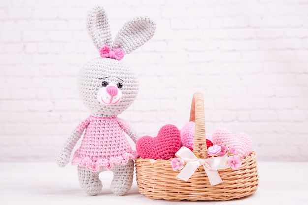 Wicker basket with multi-colored knitted hearts. knitted rabbit. festive decor. valentine's day. handmade, knitted toy, amigurumi