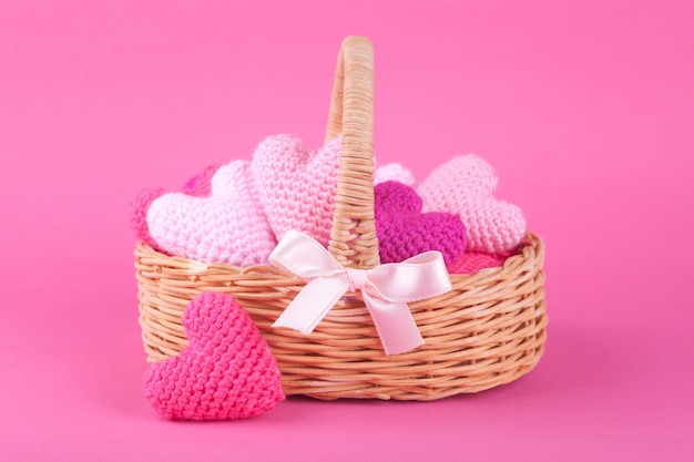 Wicker basket with multi-colored knitted hearts