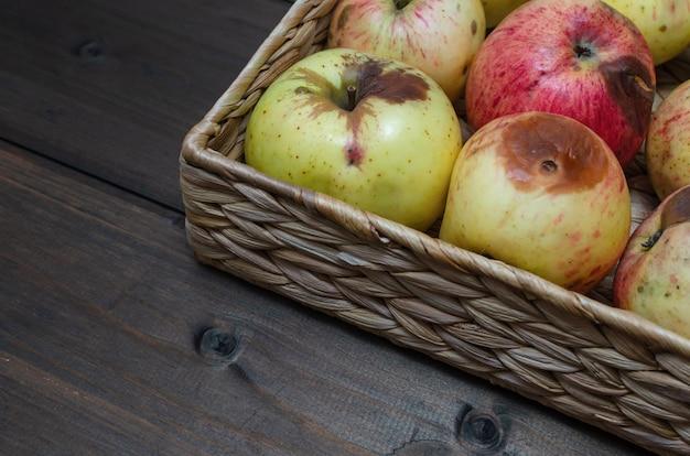 Плетеная корзина с органическими уродливыми яблоками на деревянном коричневом столе. закрыть