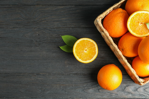 Wicker basket with ripe oranges on wooden table.