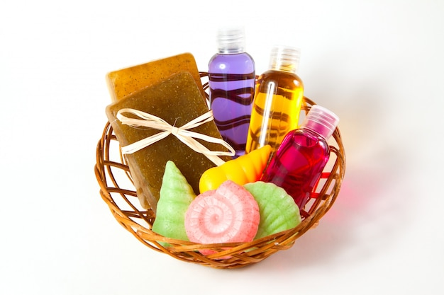 Wicker basket with soap, gel and other accessories for taking a bath and shower on a white