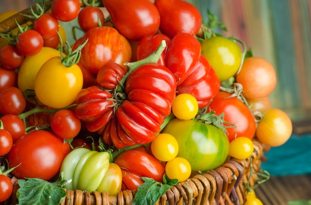 Плетеная корзина с различными красочными овощами. свежие красные помидоры в корзине на кухне