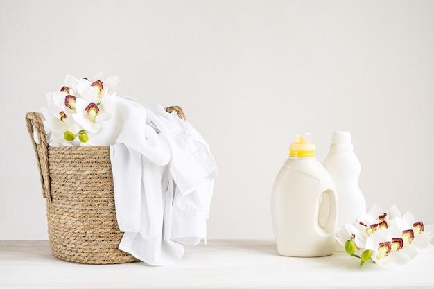 난초 꽃과 흰색 테이블에 흰색 리넨, 세척 젤 및 섬유 유연제 바구니. 복사 공간 모형 세탁의 날.
